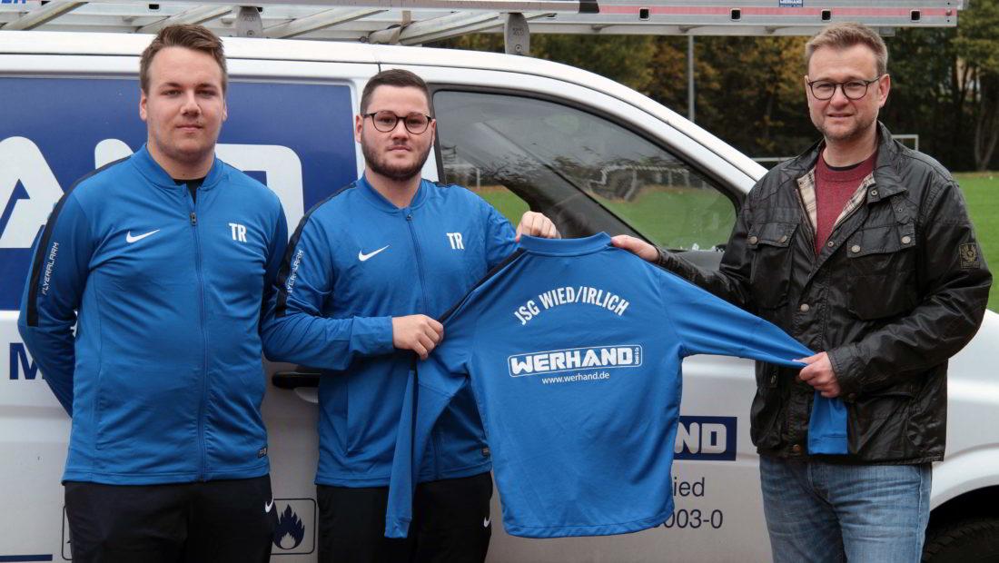 Peter Werhand (re) übergibt Philipp Pfeiffer (li) und Marcos Becker, den beiden Trainern der D-Jugend von der JSG Wied/Irlich, die neuen Trainingsanzüge und Shirts.